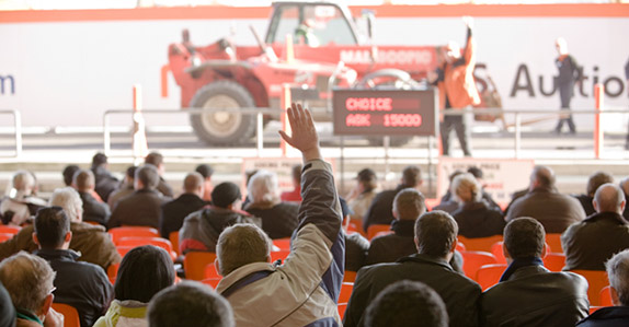 Buyers place bids as equipment is driven across the ramp